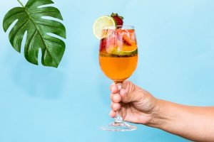 hand holding cocktail drink with blue background