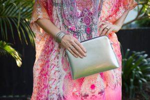 woman wearing colourful dress and silver handbag