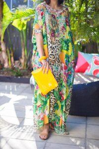 woman wearing colourful dress and yellow handbag