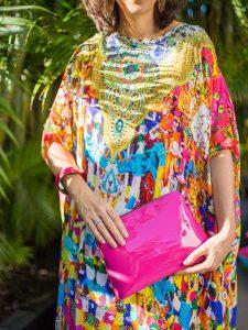 woman wearing colourful dress and pink handbag