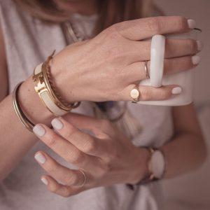woman wearing fashion jewellery and holding mug