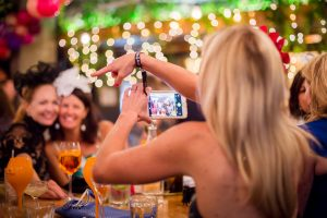 woman taking photo with smartphone at a function