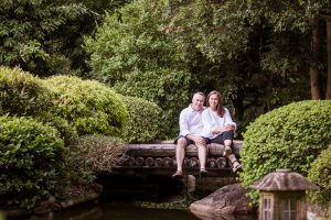 couple sitting on a bridge in the park