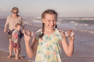 girl collecting shells on the beach portrait