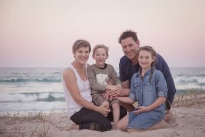 family sitting on the beach portrait