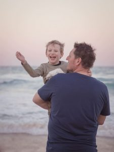 father holding son on beach portrait