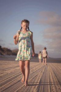 girl walking along beach portrait
