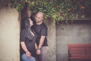 couple standing against wall with greenery