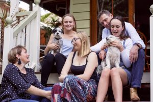 family with dogs sitting on porch