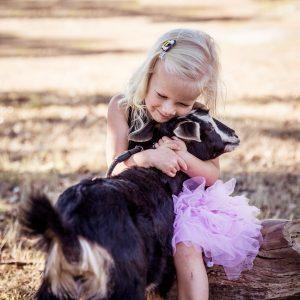 little girl hugging goat