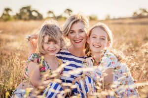mother and daughters sitting in a field