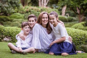 mother and children sitting in the park portrait