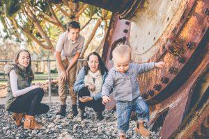 mother and children watching toddler walking portrait