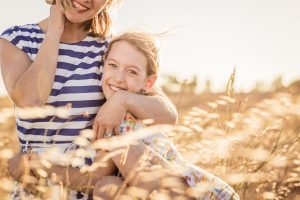 mother and daughter sitting in a field portrait