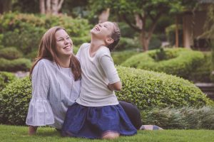 mother and daughter sitting in a park portrait