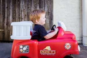 toddler sitting in red car portrait